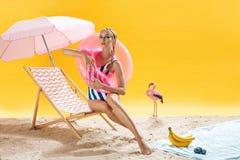 Фотомодель с розовым кругом заплывания представляет на желтой предпосылке Стоковая Фотография