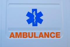 Фотоснимок знака автомобиля машины скорой помощи и текст на белизне Чрезвычайные обслуживани Стоковые Фотографии RF