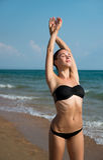 Фотоснимок красивой женщины ослабляя на пляже в волне Стоковая Фотография