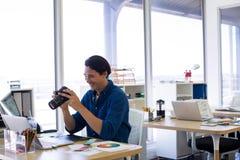 Фотоснимок мужской исполнительной власти рассматривая захваченный на его столе Стоковая Фотография