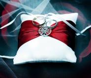 Фотоснимок обручальных колец на белой подушке с красной лентой Стоковое Изображение RF