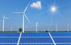 фотоэлементы и ветротурбины производя электричество в электростанции на предпосылке голубого неба Стоковые Фото