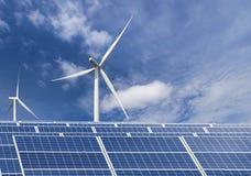 Фотоэлементы при ветротурбины производя электричество в гибридной станции систем электростанции на предпосылке голубого неба стоковые изображения