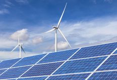 Фотоэлементы при ветротурбины производя электричество в гибридной станции систем электростанции на предпосылке голубого неба стоковые фотографии rf