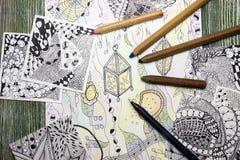 Фото абстрактного фонарика doodle сделанного из черной ручки вкладыша и используемых карандашей на деревянном столе Ходы ручки Do Стоковые Фотографии RF
