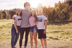 Фото близких другов стоит внешним, имеет пикник совместно, обнимает и усмехается счастливо на камере, имеет хорошее отношение, од стоковые фотографии rf