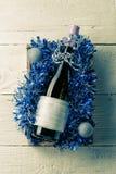Фото бутылки вина с пустой карточкой в коробке с сусалью, Стоковое Изображение RF