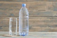 Фото бутылки с водой с стеклом на деревянном столе стоковое изображение rf