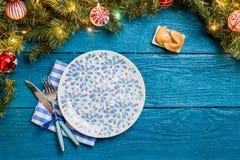 Фото ветвей ели, печений с прогнозом, плит Нового Года, вилок, ножа, салфетки Стоковое Изображение RF
