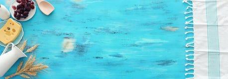 Фото взгляда сверху молочных продучтов над голубой деревянной предпосылкой Символы еврейского праздника - Shavuot стоковое изображение rf