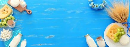 Фото взгляда сверху молочных продучтов над голубой деревянной предпосылкой Символы еврейского праздника - Shavuot стоковые изображения