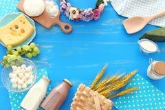 Фото взгляда сверху молочных продучтов над голубой деревянной предпосылкой Символы еврейского праздника - Shavuot стоковые изображения rf