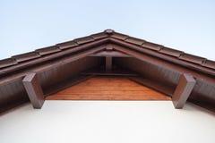 Фото взгляда сверху низкого угла элементов коричневого угла крыши деревянных поверх небольшого удобного дома с белыми стенами стоковое фото