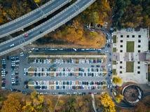 Фото взгляда сверху парковки около моста парка транспортной развязки и города принятого трутнем стоковая фотография