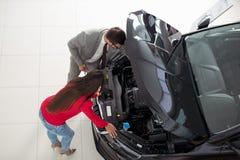 Фото взгляд сверху молодого мужского консультанта и покупатели подписывая контракт для нового автомобиля Стоковая Фотография