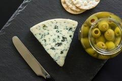 Фото взгляд сверху сыра Stilton голубого, опарника заполненных оливок и Стоковое Изображение