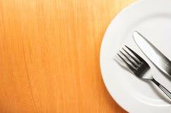 Фото вилки и нож с белой плитой на wo Стоковое Изображение RF