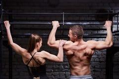 Фото вид сзади мышечного человека и женщины делая тренировки на турнике против кирпичной стены на спортзале креста подходящем Стоковые Фото