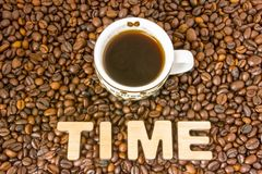 Фото времени кофе Кружка с заваренным кофе окружена зажаренным в духовке всем деревом кофе зерен при время слова, составленное 3D Стоковые Фотографии RF