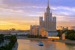Фото высокого здания стоя на банке реки Moskva на заходе солнца Стоковая Фотография RF