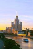 Фото высокого здания стоя на банке реки Moskva на заходе солнца Стоковые Изображения RF