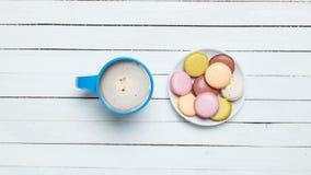 Фото голубых чашки кофе и плиты вполне macaroons на w Стоковая Фотография