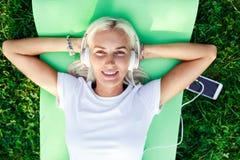 Фото девушки в наушниках на лужайке Стоковые Изображения RF