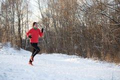 Фото девушки в спорт равномерных на утре бежит в лесе зимы Стоковое Изображение RF