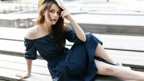 Фото девушки в шляпе сидя на деревянной скамье Стоковое Фото