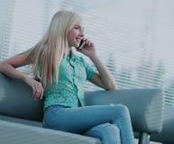 Фото девушки говоря на телефоне и смотря вне окно Стоковая Фотография RF