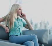 Фото девушки говоря на телефоне и смотря вне окно Стоковые Фото