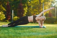 Фото девушки делая йогу вычисляет на траве Стоковые Изображения RF