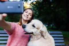Фото девушки на стенде делая selfie с retriever Стоковая Фотография