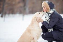 Фото девушки обнимая labrador в снежном парке Стоковые Изображения