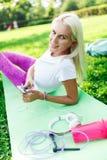 Фото девушки спорт с телефоном на половике Стоковая Фотография RF