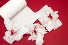 Фото 3 дерьм использовало кровопролитные туалетную бумагу и крен туалетной бумаги на красной предпосылке Менструальный, кровоточи Стоковые Изображения