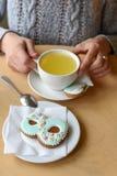 Фото дня ` s женщин рук ` s женщины, бака чая, чашки и печенья сформировало как диаграмма ` ` 8 Стоковые Фотографии RF