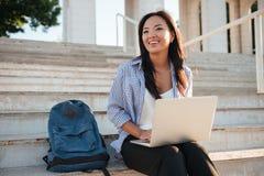 Фото довольно азиатской женщины, держащ компьтер-книжку, смотря в сторону, sitt стоковые фотографии rf