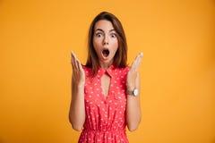 Фото довольно сотрясенной эмоционально женщины в красном платье смотря a Стоковое Фото