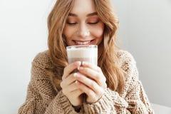 Фото европейского привлекательного стекла женщины 20s выпивая latte, стоковое фото rf