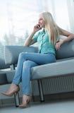 Фото девушки говоря на телефоне и смотря вне окно Стоковое Изображение