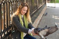 Фото девушки и голубей Подавая голуби в парке Стоковое Изображение