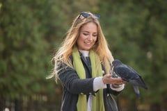 Фото девушки и голубей Подавая голуби в парке Стоковые Фотографии RF