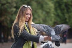 Фото девушки и голубей Подавая голуби в парке Стоковая Фотография RF