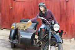 Фото девушки на винтажном мотоцилк в пилотной крышке с котом Стоковое Фото