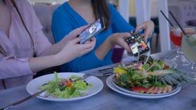 Фото еды на смартфоне, девушках блоггеров фотографирует красивая полезная еда на сотовом телефоне во время завтрак-обеда во время видеоматериал