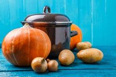 Фото железного бака с крышкой, овощами, картошками, тыквами, луками Стоковое фото RF