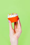 Фото женской руки держа пирожное на чудесной задней части зеленого цвета Стоковая Фотография RF