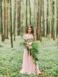 Фото женщины в платье пинка свадьбы смотря большой букет красных, белых цветков и зеленой травы на Стоковые Изображения RF