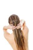 Фото женщины прикладывая проводник волос Стоковое Изображение